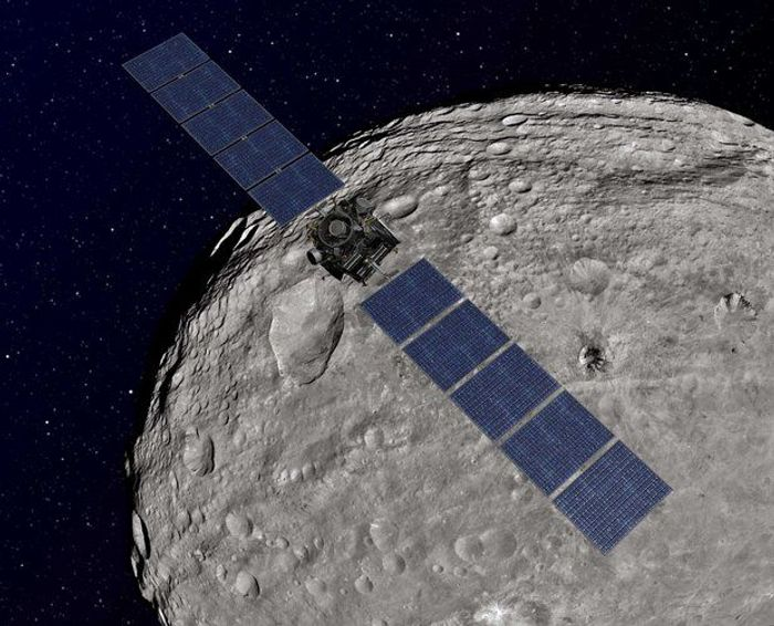 NASA's artist image shows the Dawn probe orbiting the asteroid Vesta en route to Ceres orbit