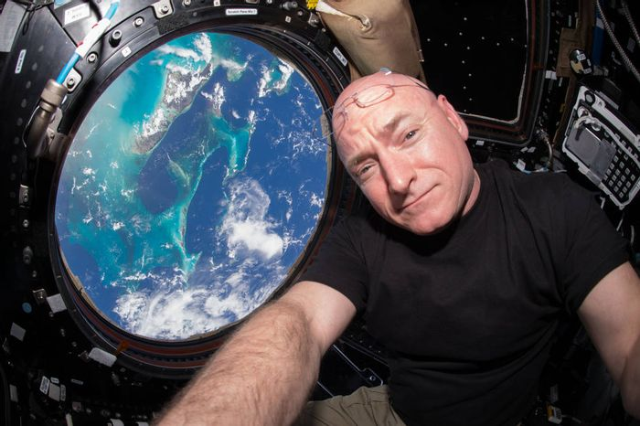 Scott Kelly poses for a selfie in space with the Earth in the background.
