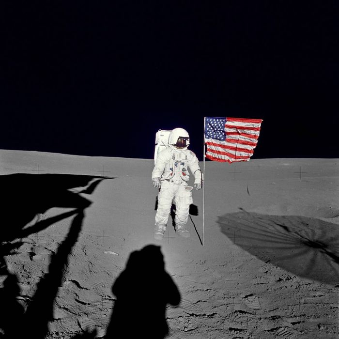 Mitchell stands beside an American flag on the Moon's surface.