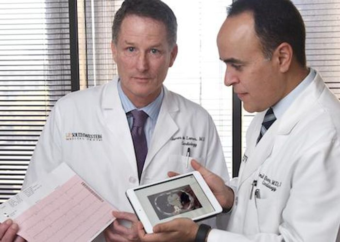 Cardiologists Dr. James de Lemos (left) and Dr. Amit Khera (right) review a printout from an EKG and a calcium scan. Credit: UT Southwestern