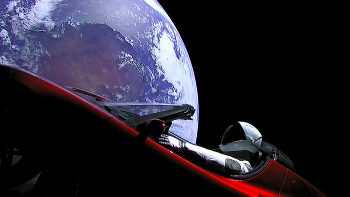 Elon Musk's cherry red Tesla Roadster floating in space as seen from cameras mounted on the car itself.