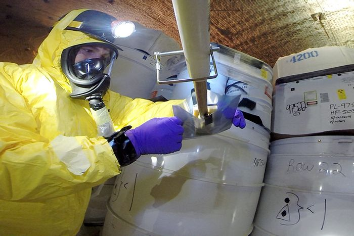 A recovery worker obtains samples from a damaged drum after a safety incident in May 2014 at the Waste Isolation Pilot Plant in New Mexico.