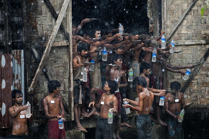 Bangladeshi and Rohingya migrants who were found drifting at sea collect rain water at a temporary shelter in Myanmar's northern Rakhine state. Photo: AFP