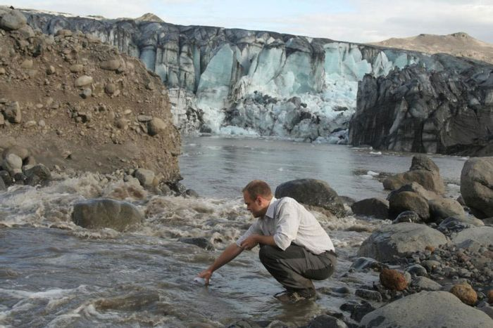 Dr. Peter Wynn collects meltwater samples. Photo: Yale E360