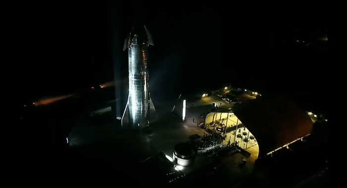 SpaceX's Starhopper spacecraft stands tall behind a stage where Elon Musk talked about the company's future endeavors.