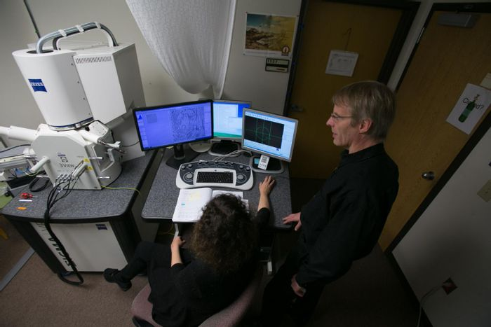 Drs. Cirelli, foreground, and Tononi, right, study an image of a mouse brain taken by a scanning electron microscope, left. Thousands of these images were analyzed for the study published this week in the journal Science. / Credit: John Maniaci/UW Health