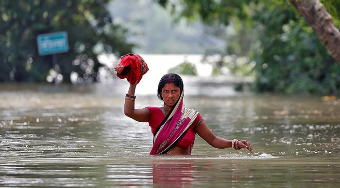 A woman wades through a flooded village in the eastern state of Bihar, India August 22, 2017. © Cathal McNaughton / Reuters.