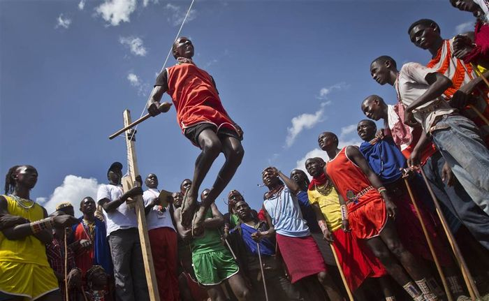 A Maasai warrior makes the high jump, not in Olympic fashion but in Maasai warrior-style, a vertical jump from a standing position. Athletes must touch a high line with the top of their heads.  Photo: Ben Curtis/AP