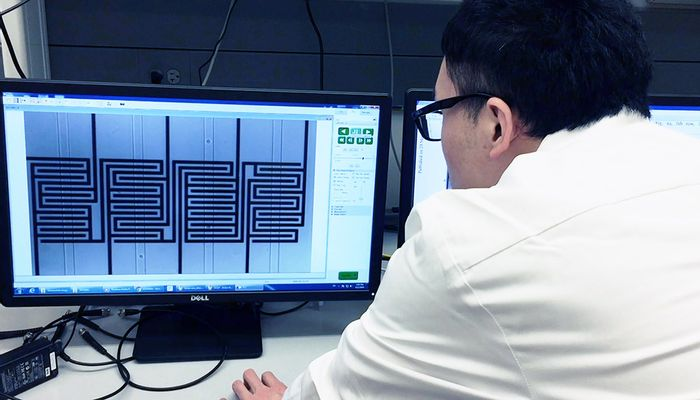 A researcher watches ovarian cancer cells move through a chip. The microfluidic channels are vertical; the circuit pattern is shown behind them.