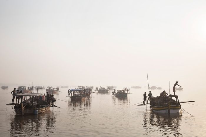 Sanding mining boats work illegally on the Thane Creek in Maharashtra, India. Workers dive to the bottom with a metal bucket to scoop sand; the boat crew hauls it to the surface.