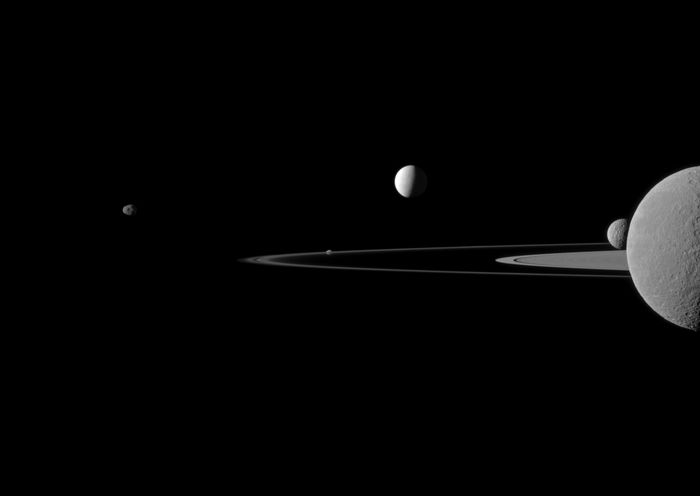 An image taken by the Cassini spacecraft of some of Saturn's moons orbiting the planet.